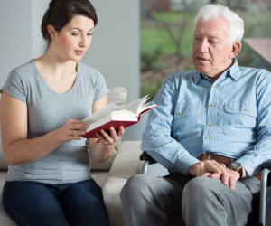 caregiver reading a book to patient